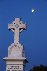 Celtic wheel cross atop a tall grave memorial